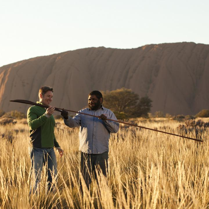 an indigenous man showing a tourist an atlatl