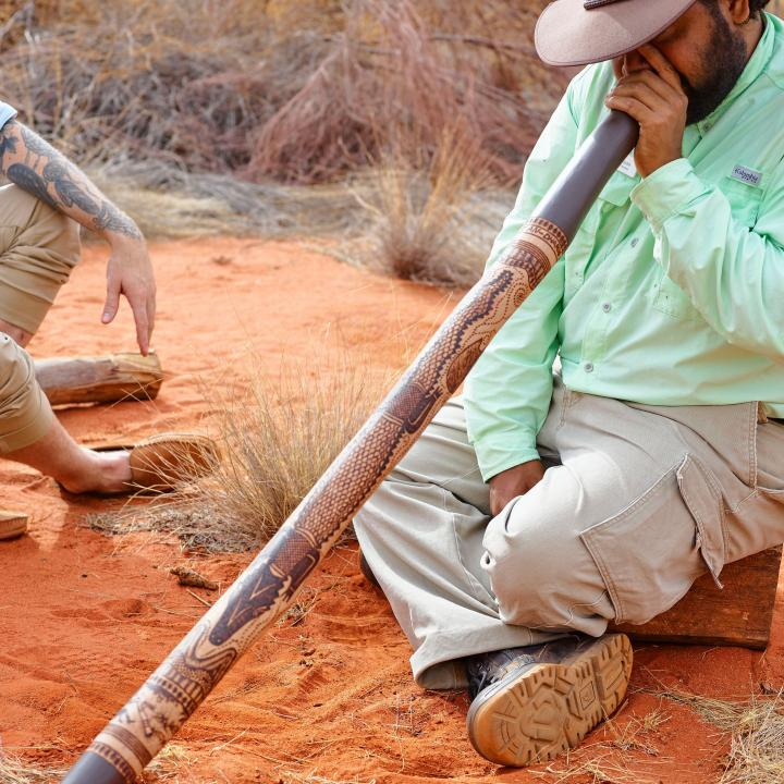 Didgeridoo being played by man in the outback