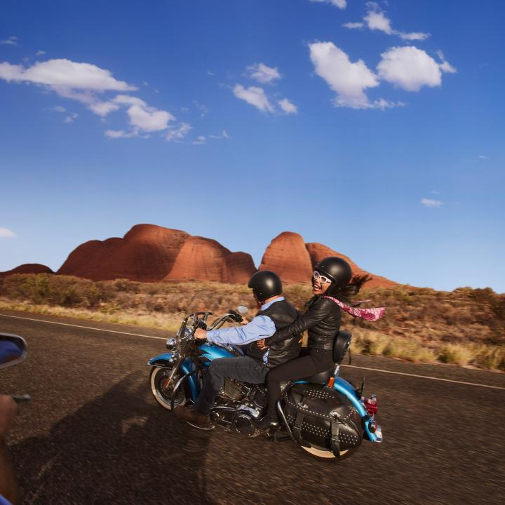 couple riding on the back of a Harley with Uluru in the background