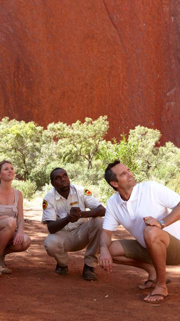 people crouched in the shadows of Ayers Rock