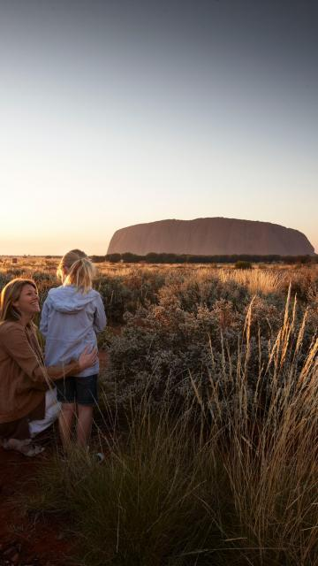 A family looking at Ayer's Rock at sunset