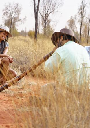 indigenous man playing the didgeridoo